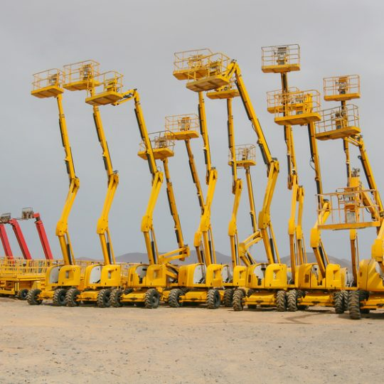 Several colorful self propelled wheeled hydraulic articulated boom lifts with telescoping boom and yellow basket on a desert landscape background